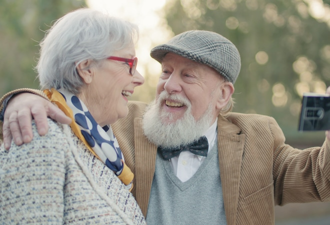 Old man smiles happily to old woman